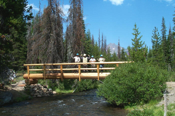 Usfs trail crew builds a log bridge over fall creek at green lakes